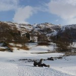 Snowy Loughrigg Tarn at the foot of Loughrigg Fell, Lake District