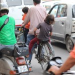 Father and children cycle in traffic, New Delhi, road